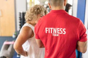 Gym Plus Staff Member talking to a member