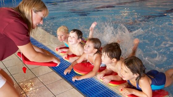 Swim instructor talks to children at Gym Plus